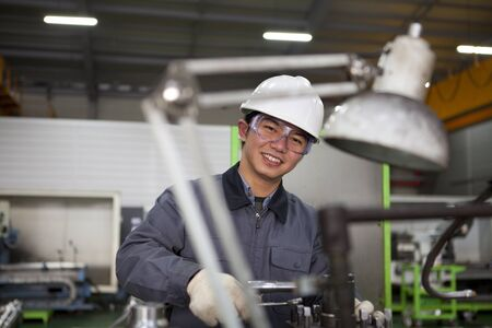 skilled labour: modern industrial machine operator working in factory  Stock Photo