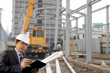 industrial site: young architect standing front of construction site