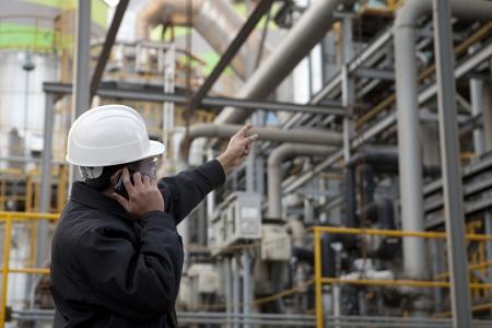 ingénieur raffinerie de pétrole pointant contre pipeline