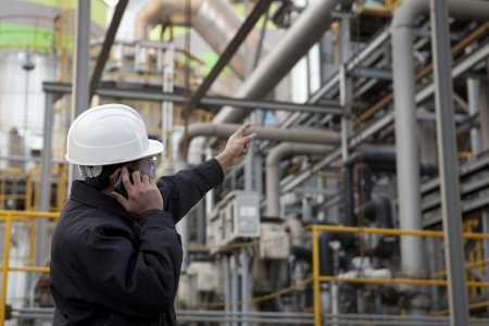 maintenance engineer: oil refinery engineer pointing against pipeline