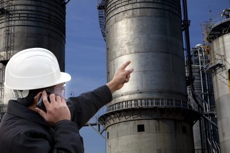 engineer calling and pointing to a large oil refinery photo