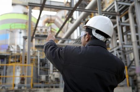oil refinery engineer pointing against pipeline Reklamní fotografie - 17232092