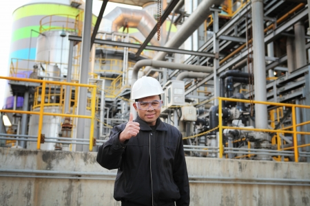 industrial engineer with thumbs up standing beside pipeline inside oil refinery Standard-Bild