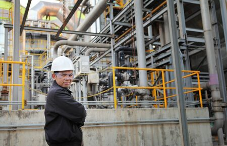 engineer standing beside pipeline inside oil refinery photo