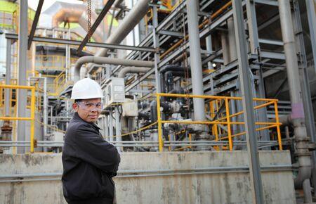 engineer standing beside pipeline inside oil refinery Standard-Bild