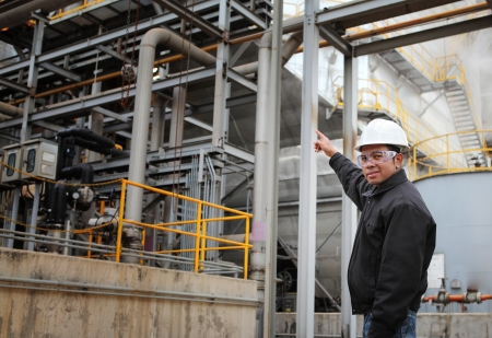 engineer pointing against pipeline inside oil refinery photo