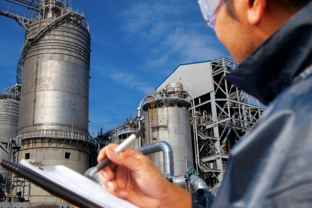 steel factory: engineer oil refinery write on the notes book looking large oil refinery focus on refinery