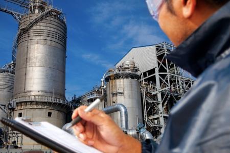 industria petroquimica: refinería de petróleo ingeniero escribir en el libro de notas mirando foco grande refinería de petróleo en la refinería