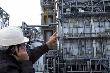 engineer pointing examining against pipeline inside oil refinery photo