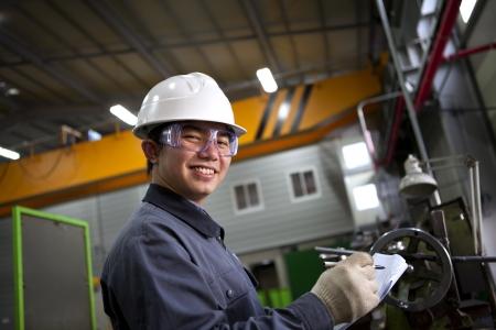 operante: scrittura tecnico meccanico sul blocco note in fabbrica