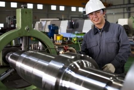 manufactura: t�cnico operativo asi�tico del centro cnc fresadora de corte en el taller de la herramienta Foto de archivo