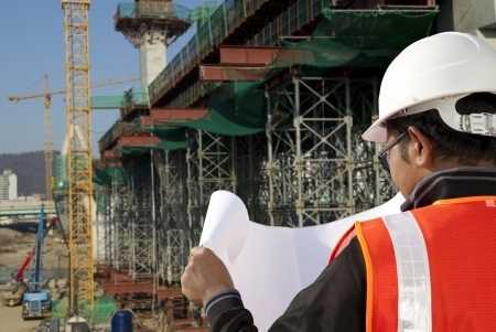 foremaster: builder inspector checking plan a construction site