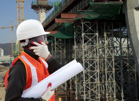 jobsite: Engineer On A Construction Site Using A Mobile Cellphone
