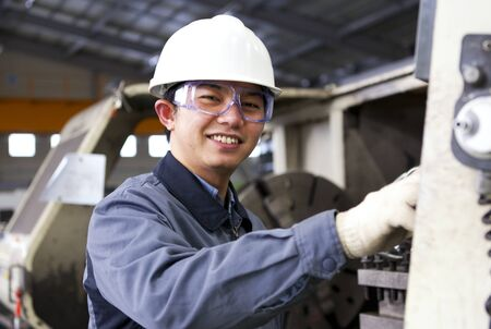 Technician working in factory front of milling cutting machine photo