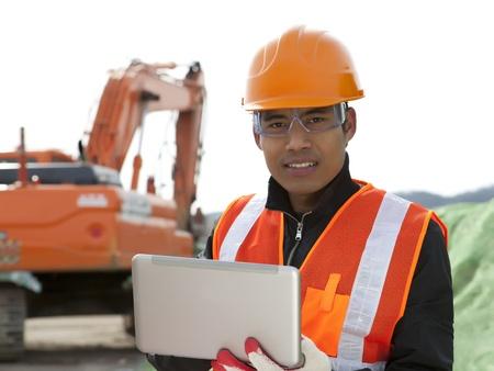 road construction worker using laptop standing front excavator