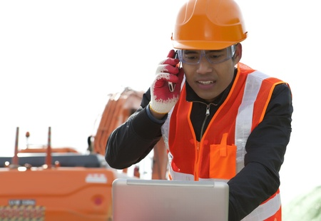 heavy equipment operator: road construction worker talking on mobile phone and using laptop computer standing front excavator Stock Photo