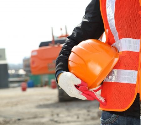 safety vest: construction safety concept with exavator background