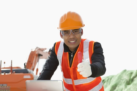 building safety: road construction worker with showing thumb up using laptop standing front excavator