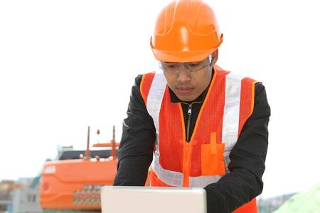 heavy equipment operator: road construction worker using laptop standing front excavator