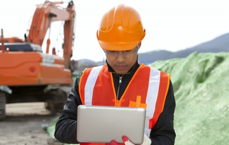 road construction worker using laptop standing front excavator Stock Photo - 18062199