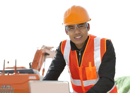 road construction worker using laptop standing front excavator Stock Photo - 18062203