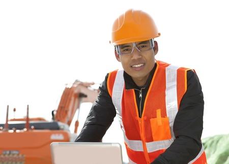road construction worker using laptop standing front excavator Stock Photo - 18062203