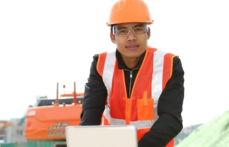 road construction worker using laptop standing front excavator Stock Photo - 18062185