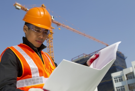 construction worker checking a blueprint with crane on the background