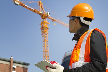 construction crane: construction worker checking location site with crane on the background