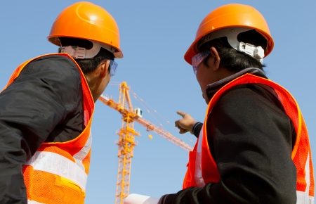 Site manager with safety vest discussion under construction Standard-Bild