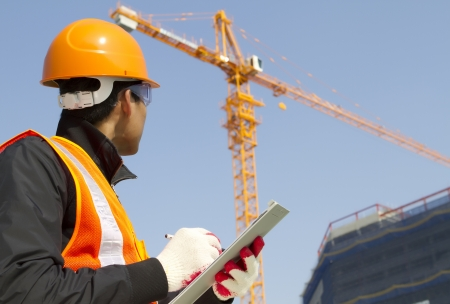 construction helmet: construction worker on location site with crane on the background Stock Photo