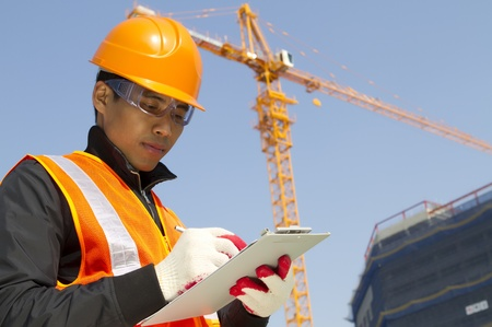 dynamic activity: construction worker checking a document with crane on the background