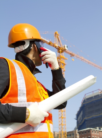 construction worker talking in mobile phone with crane in background