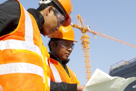 asian architect:  construction workers  discussion on location site with crane in background