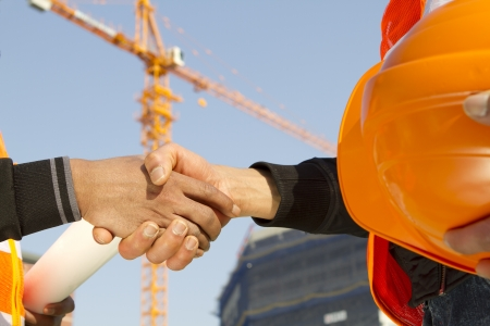 industrial site: construction workers handshake closing a deal with crane on the background