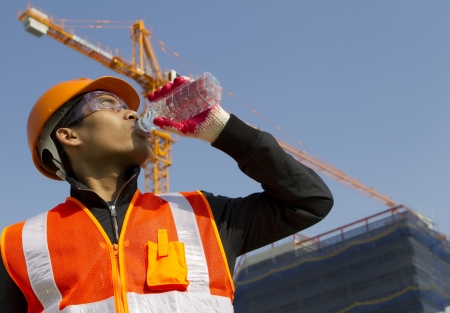 worker man  as he drinks from a plastic water bottle on construction site photo