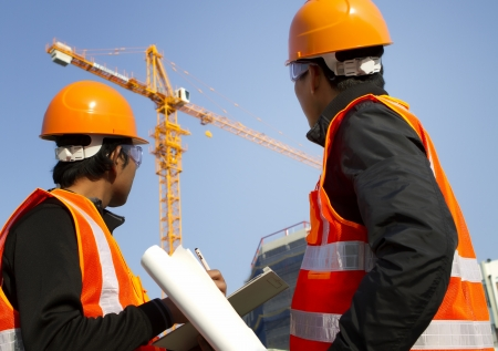 Site manager with safety vest discussion under construction Imagens