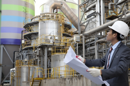 plant oil: engineer oil refinery with blueprint on location site Stock Photo