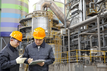 oil mill: two engineer discussing a new project with large industry background