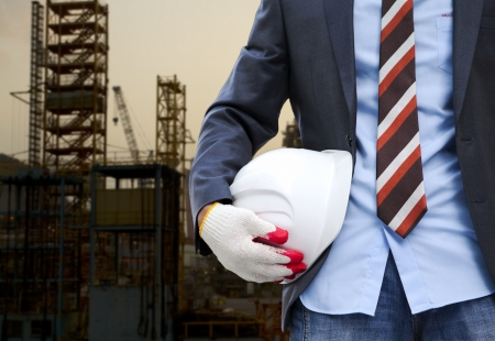 Construction safety concept. Close up view architect holding white helmet on dusk day with crane and building construction on the background