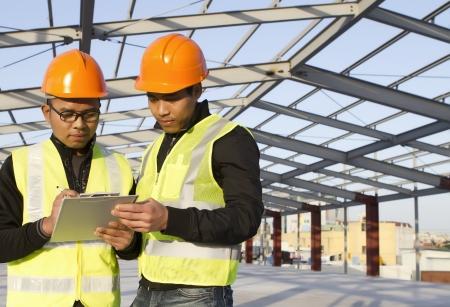 ingénieurs en construction avec discussion de gilet de sécurité sur le site de localisation Banque d'images