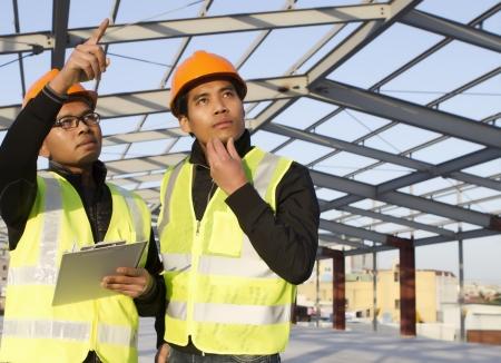 ingeniero civil: ingenieros de la construcci�n con chaleco de seguridad discusi�n en el sitio de ubicaci�n Foto de archivo