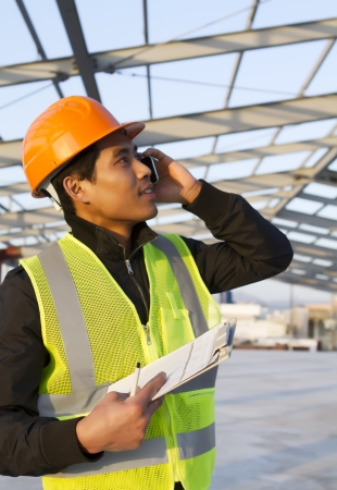 Engineer construction talking mobile phone under new building checking plan photo