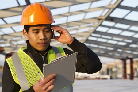Engineer construction talking mobile phone under new building  photo