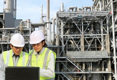 engineer oil refinery discussion with laptop on location site Imagens