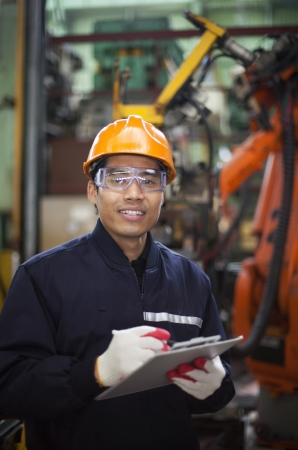 Portrait of engineer writing on a clipboard in a factory