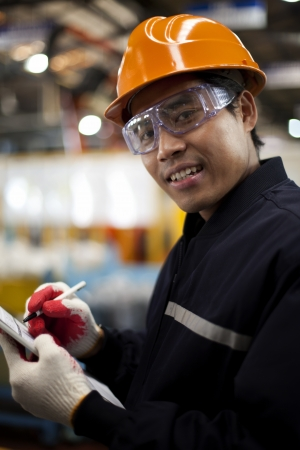 Portrait of engineer writing on a clipboard in a factory photo