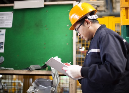 Portrait of asian engineer checking technical data in the factory photo