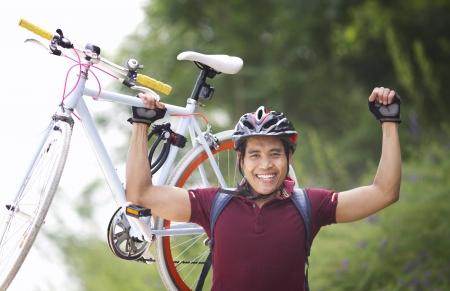 Heureux l'homme soulevant un vélo