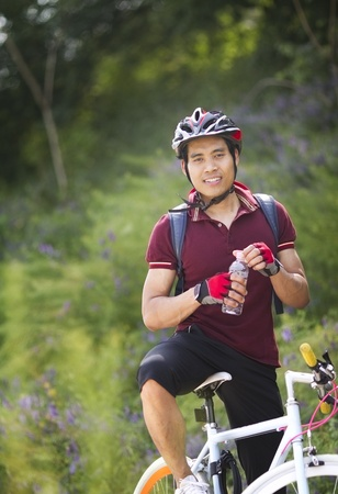 Young male cyclist holding bottle of water  photo